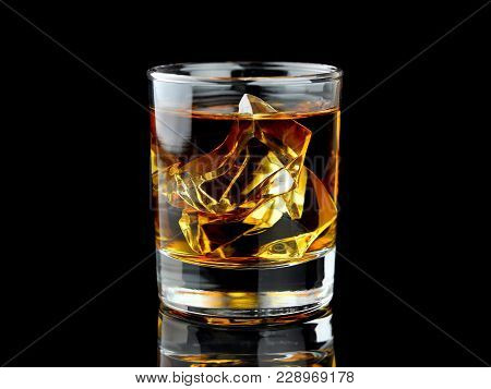 Glass Of Whiskey With Ice On Black Background With Reflection. Close Up View. Selective Focus On Ice