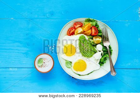 Healthy Vegetarian Breakfast Plate Flat-lay. Fried Eggs, Avocado And Fresh Vegetables On Blue Wooden