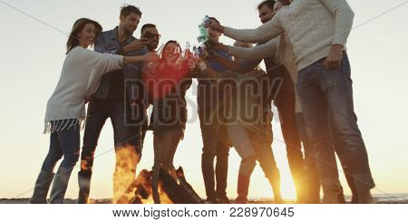 Young Friends Making A Toast With Beer and having fun Around Campfire at beach party on autumn day
