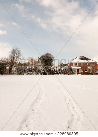 Field Covered In Snow With Two Tracks Through It Landscape; Essex; England; Uk