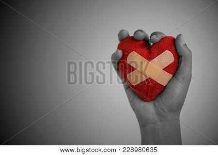 Close Up Young Woman Hand Holding Red Heart Glued By Cushioned Plaster Strip Medical Patch On Wooden