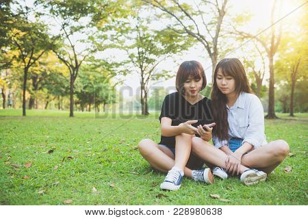 Two Beautiful Happy Young Asian Women Friends Having Fun Together At Park And Taking A Selfie. Happy
