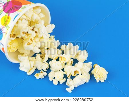 Popcorn Is Poured From A Multi-colored Paper Cup On A Blue Table. Vegetarian Food From Corn.