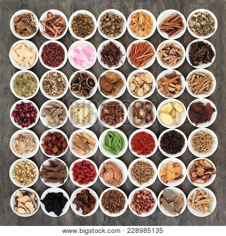 Traditional chinese medicine selection with a large collection of herbs in white porcelain bowls on marble background.