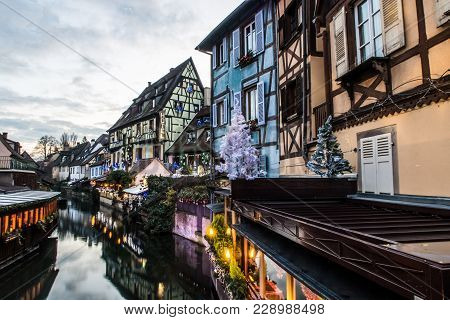 Street Above A Canal In The French City Of Colmar. Old Typical Colorful Architecture At Sunset.