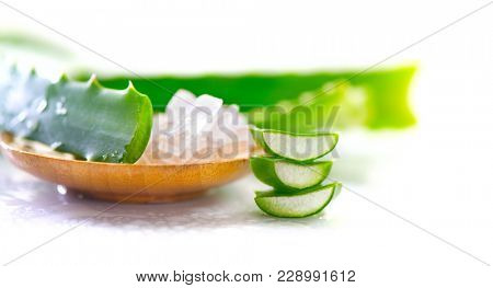 Aloe Vera gel closeup. Sliced aloevera leaf and gel, natural organic cosmetic ingredients for sensitive skin, alternative medicine. Organic Skin care concept. On white wooden background