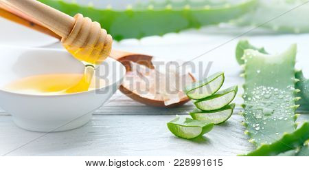 Aloe Vera and honey closeup. Sliced Aloevera with dripping honey natural organic cosmetic ingredients for sensitive skin, alternative medicine. Organic Skin care concept. On white wooden background