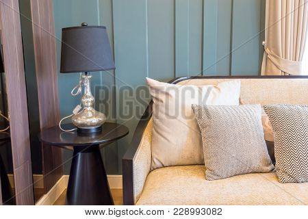 An Interior Picture Of A Light Brown Pillows On Beige Fabric Sofa And A Luxury Lamp On Wooden Table