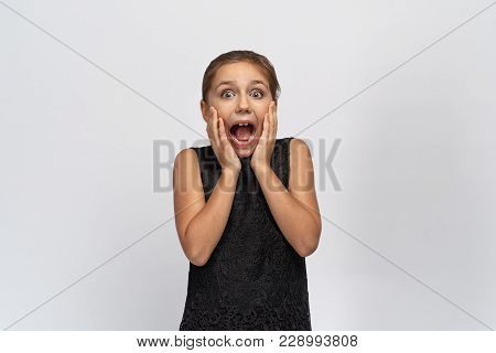 Young Beautiful Little Girl Covers Her Mouth In Shock, Emotionally Looks With Great Surprise At The