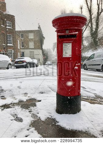 HAMPSTEAD, LONDON - FEBRUARY 28, 2018: Royal Mail Red Pillar Postbox on a snowy day in Hampstead, North London, UK.