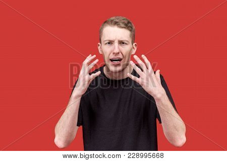 Emotional Young Caucasian Man In A Black T-shirt Actively Gesticulating Hands With An Indignant Diss