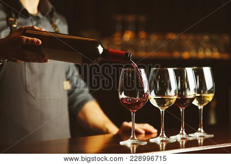 Bartender In Apron Pours Sweet Red Wine From Bottle In Capacious Glasses On Wooden Bar Counter. Deli
