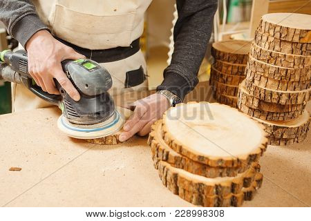 Male Holding Wooden Round Workpiece And Processing With Grinding Machine Using Abrasive Wheel As Cut