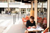 aged female screenwriter sitting in outdoor cafe and reproduce scenario from paper drafts in text file on laptop. Lady dressed in black cardigan looks like very pleased with work. Woman scans pages and removes lying glasses aside. poster