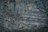 Close-yp grunge fantastic gray-blue stone wall with uneven hollowed-out surface. poster