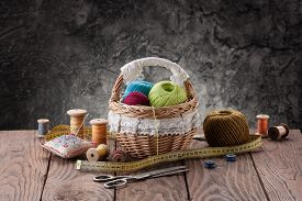 Tangles Of Thread In A Basket, Scissors And Threads In Reels On A Background Of Wooden Boards