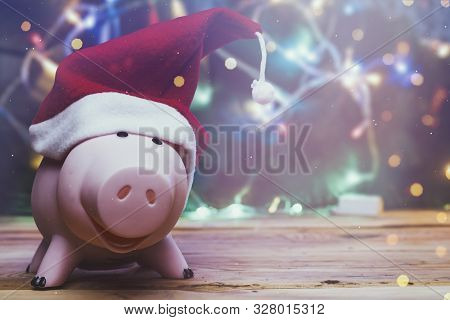 Piggybank With Santa Claus Cap Against Decorated Xmas Tree. Christmas Shopping. Saving Money For Chr