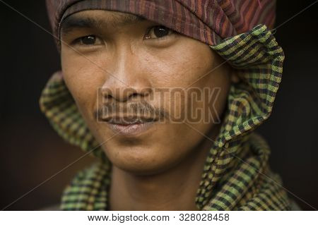 Phnom Pehn, Cambodia - January 22, 2011: Smiling Young Cambodian Man Uses Checkered Headscarf In The
