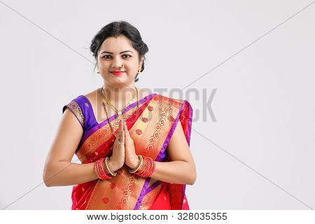 Young Indian Woman Wearing  Sari  And Showing A Welcome Gestures, Isolated On White Background