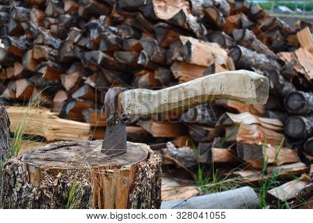 Old Axe With Wooden Handle On Stub. To Cut And Prepare Firewood For Winter. Woodpile With Firewood A