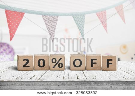 Special Price 20 Percent Off Promotion Sign On A Desk With Colorful Flags Above