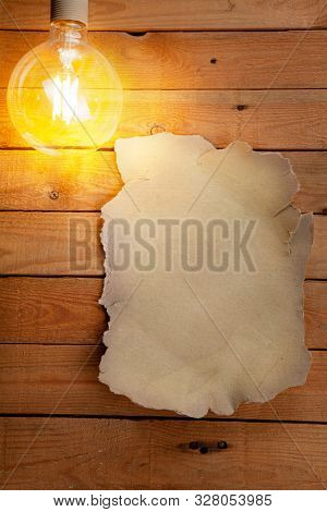 Old sheet of paper on a wooden table. Space for a text. Light bulb.