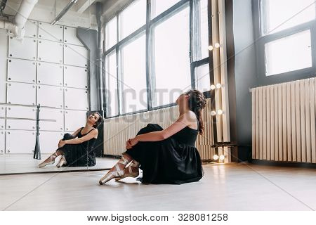 Dancing Hall. Nice Elegant Ballet Dancer Sitting In Front Of The Mirror While Practicing In The Danc