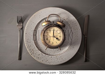 concept of intermittent fasting, ketogenic diet, weight loss. fork and knife, alarmclock on plate
