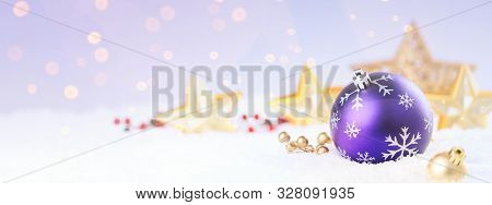 Purple Christmas Ball On The Snow Over Blurry Background.