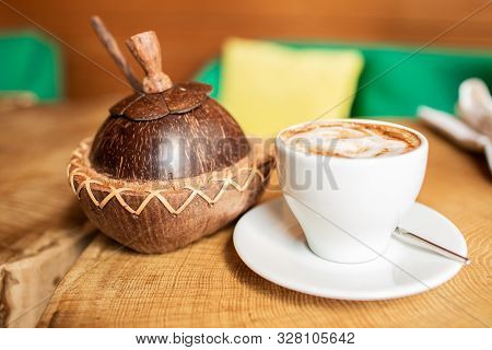 Original Coconut Sugar Bowl. A Cup Of Coffee On A Wooden Table.