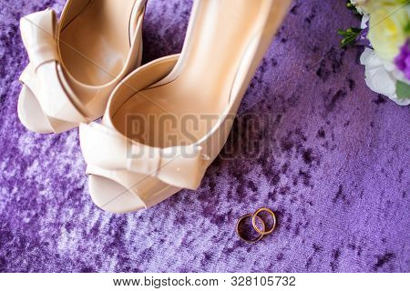 Beautiful Wedding Bouquet Of Flowers, Rings And Bridal Shoes On Lilac Background. Wedding Rings. Wed
