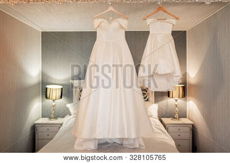 White Wedding Dress Of The Bride In The Bedroom.
