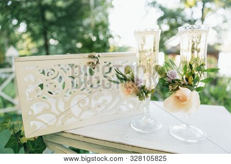 Two Glasses With Champagne For The Bride And Groom. Wedding Decor From Fresh Flowers.