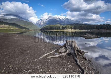A Stump Sits In The Foreground At Mission Reservoir And High Peak Snow Covered Mountains Near St. Ig