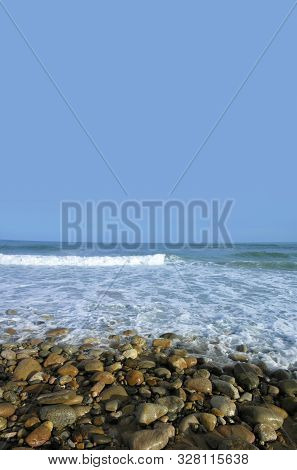 Oceanside Wet Rocky Beach With Water Waves  And Clear Blue Sky