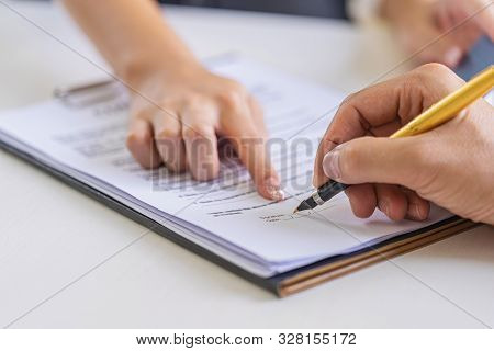 Estate Agent Pointing Finger On Document Showing Where To Sign. Signing A Paper Document For Buying