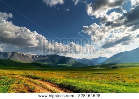 Panoramic Landscape Of The Mountain Range. Green Mountain Pass On A Sunny Day With Clouds.