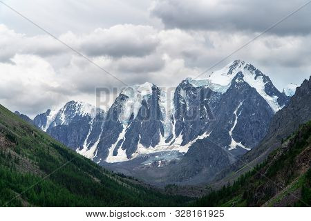 Landscape Of Snowy Mountain Peaks In The Clouds. The Concept Of Global Warming And Glacier Melting.