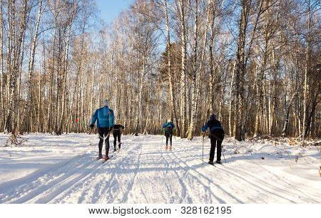 A Group Of People Skiing In A Winter Park. Sunny Day, Competitive Spirit And Support.
