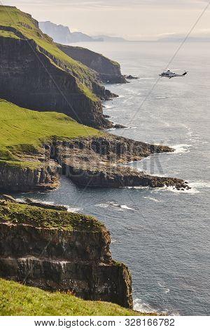 Helicopter Flying Over Mykines Atlantic Cliffs In Faroe Islands. Denmark