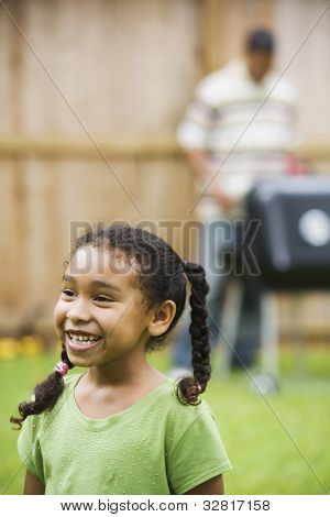 African girl with father barbequing in background