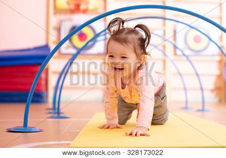Baby Toddler Crawling On Floor Through Tonnel In Gym Class. Lifestyle Concept Of Children Active Gam