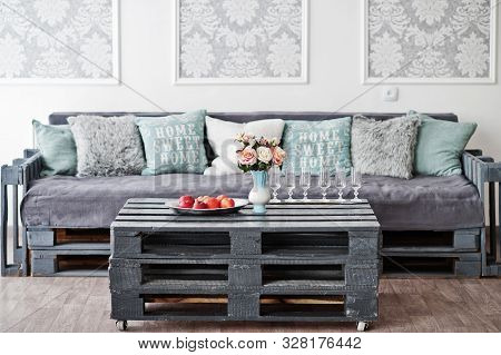 Wooden Table With Apples On It And Glasses Of Champagne Against Couch In White Room.