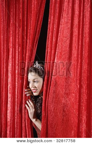 Hispanic beauty queen peeking through curtains