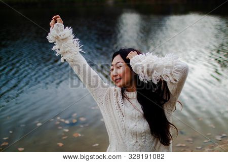 Happy Autumn Woman Blissful And Playful Smiling With Arms Out By Lake.