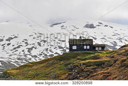 Black Nordic House In Mountains On Snow Road