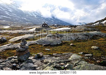Stone Pyramid And Snowy Mountains In Norway