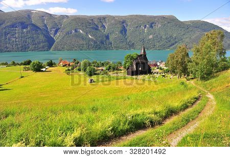 Peaceful Summer Landscape With Old Church, Green Grass Filed And Mountains