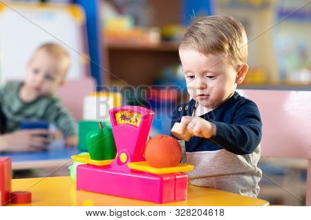 Cute Little Kid Boy Playing With Abacus In Nursery. Preschooler Having Fun With Educational Toy In D