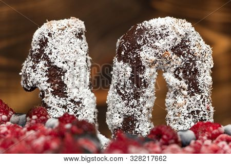Close Up Number Ten From Natural Chocolate Sprinkled With Coconut Powder Stands On Raspberry Festive